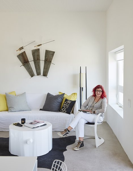 Hill sits  on a Casalino chair from Design Within Reach in the living room; on the wall is Quivers, a sculpture by her daughter, Claire Cusak. Collaborator George Sacaris made the stump table.