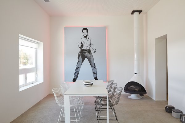 """""""Everything out here has been something else,"""" designer Barbara Hill says of Marfa, Texas. It's certainly true of her casita, which was formerly a grocery store: The 1,200-square-foot home is filled with reworked pieces, including  the Elvis artwork she embellished with pink lights fabricated by the Neon Gallery in Houston and the  refurbished Bertoia chairs from  Cast + Crew. The minimal color  palette is echoed in the freestanding  Malm fireplace and the concrete floor sculptures by William Vizcarra from Wrong Marfa."""