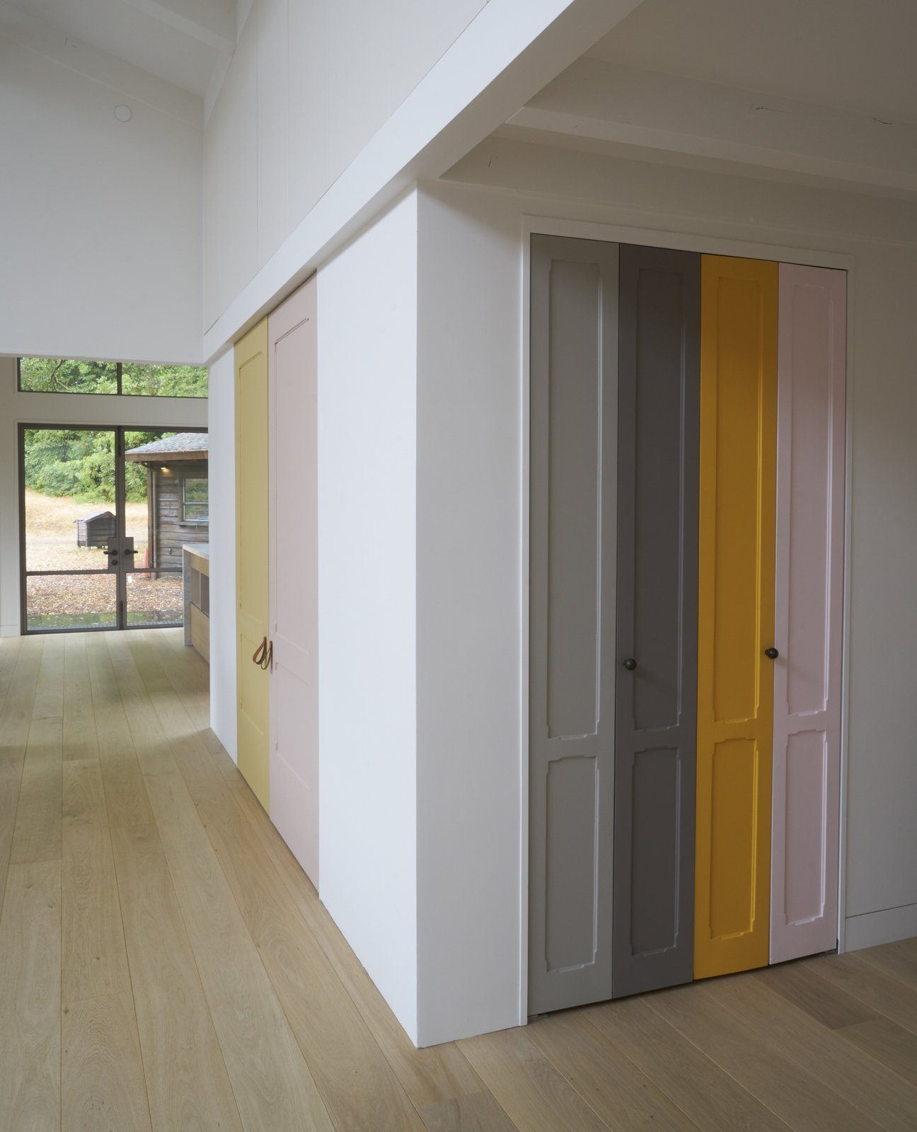 """Playful panels of color on closet doors and the stair risers break up the white walls. The homeowner explains, """"I took as inspiration Imi Knoebel, whose work I had seen at the Dia Beacon, and who works with large shapes of color placed in relationship to one another.""""   Beetlebung"""