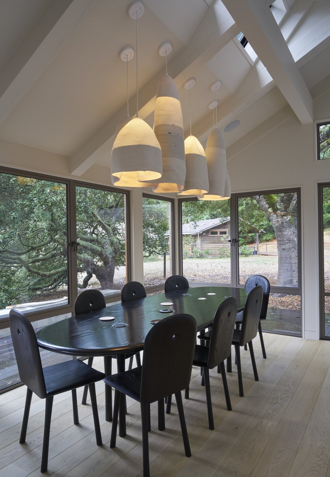 """A pendant by Doug Johnston, represented by Patrick Parrish, hangs over a custom dining table by Christopher Kurtz. """"Working with [Kurtz] was a privilege and beautiful experience,"""" says the homeowner. """"He sent us a video of a stream with eddies in it, and I thought that was so appropriate: you look out at the meadow and the forest, and the lights are kind of like mountains."""" The oval shape encourages everyone sitting around it to engage in one conversation.  Beetlebung"""