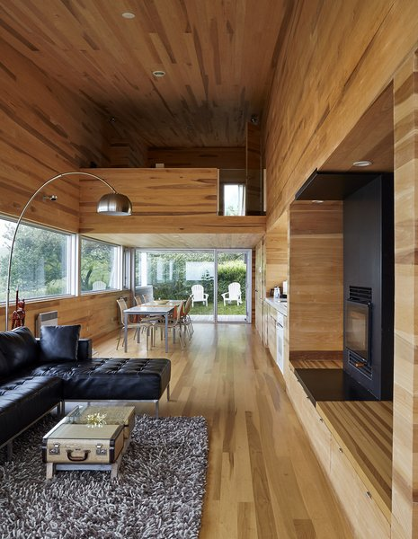 The interior of locally milled poplar contrasts with the home's metal exterior. Thanks to the six-degree pitch of the site, the dining area leads directly to the yard, while the living room ends with a balcony that's high above the ground.