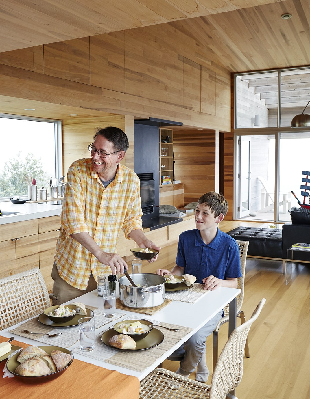 Dining Room, Table, Chair, and Light Hardwood Floor At the IKEA dining table, David Peters and his son, Dashel, enjoy a meal from a Paderno stainless-steel pot made on Prince Edward Island.  Photo 4 of 13 in Lights Will Guide You Home