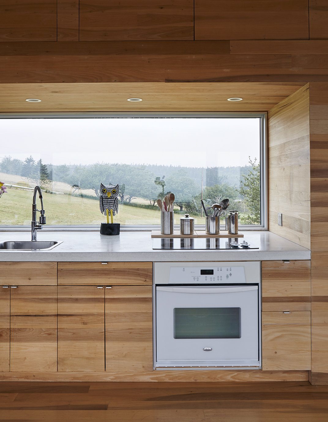 Kitchen, Drop In Sink, Wood Counter, Wood Cabinet, Cooktops, and Wall Oven The focal point of the home is the long Alumicor window that reveals the slope of the site.  Photo 5 of 13 in Lights Will Guide You Home