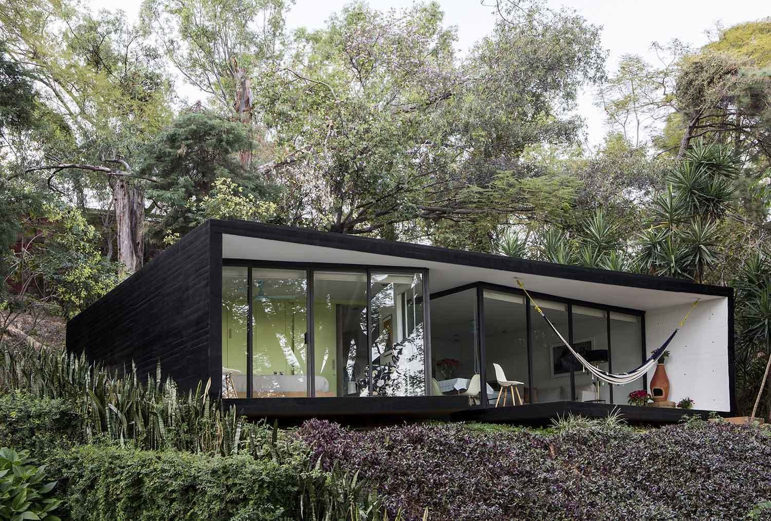 Outdoor, Shrubs, Grass, Back Yard, and Trees Constructed of steel, glass and concrete, the exteriors are clad in dramatic black with a floor to ceiling glass facade offering views of the valley below from the outdoor lounge area and pool.  Photos from 10 Modern Vacation Homes in Mexico That Guarantee an Epic Escape