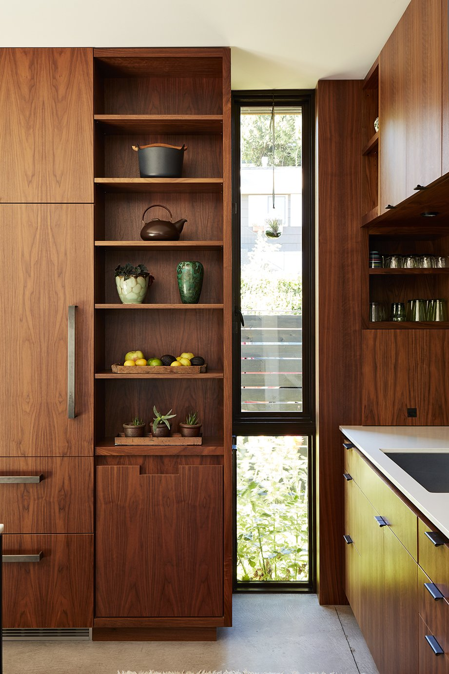 Kitchen, Wood Cabinet, Concrete Floor, and Wood Backsplashe In the kitchen, an elongated window breaks the custom walnut cabinetry by Contour Woodworks.  Photo 4 of 15 in Greener Grass