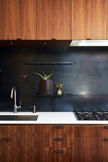 Subtly textured and tonal, a metal backsplash can be a great idea in a range of spaces, from industrial to moody and sombre. In this particular kitchen, the backsplash and drawer pulls were fabricated by 12th Avenue Iron. The cooktop is by Miele.