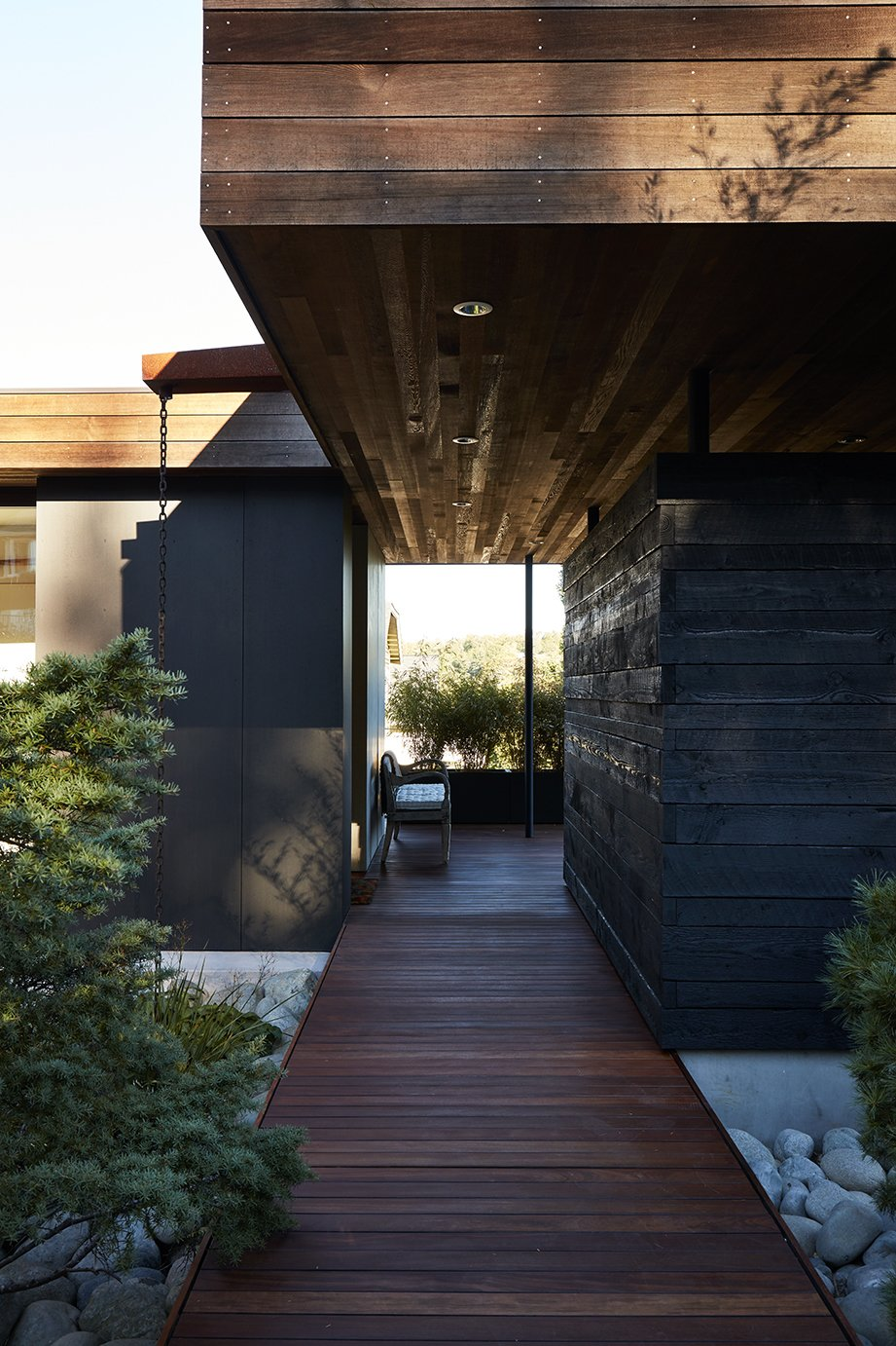 """Generous breezeways, walkways, and overhangs frame views beyond: """"It's like a promenade, with a forest at the end of the road,"""" says Deb. Tagged: Outdoor, Wood Patio, Porch, Deck, Small Patio, Porch, Deck, and Walkways.  Photo 9 of 15 in Greener Grass"""