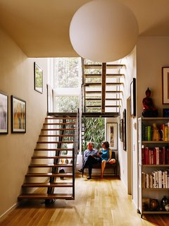 Louis did much of the woodworking in the house, including the fabrication of the  white oak stair treads. The ironwork was crafted by Alex and Gio Welding. A Glo Ball pendant by Jasper Morrison for Flos hangs in front of the staircase.