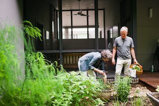 Marsha and Louis collect herbs  in a garden by their screened porch (above). The home's exterior cypress cladding is finished with Sikkens ProLuxe Cetol stain in Teak.