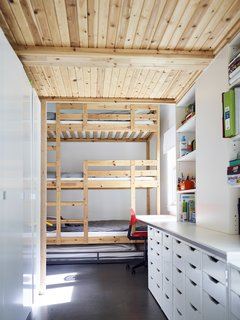 A three-level bunk bed with an additional trundle furnishes the children's room on the first floor; the cabinetry and drawers are from IKEA.
