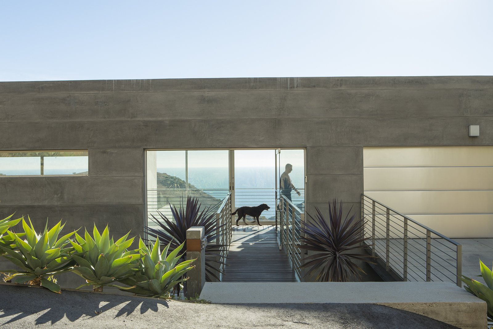 """Exterior, House Building Type, Flat RoofLine, and Concrete Siding Material """"Simple rectangular  volumes with simple details"""" is how designer Thomas Egidi describes the house he created for architect Carlos Dell'Acqua in Malibu. """"I wanted to stress its horizontality,"""" Dell'Acqua notes. Inside the dwelling, which is entered via a bridge that pierces the 25-foot-high main facade, the view  opens up to a panorama of mountains and sea. Ipe flooring is used for the walkway and throughout the interior.  Photos from Facing the Elements"""