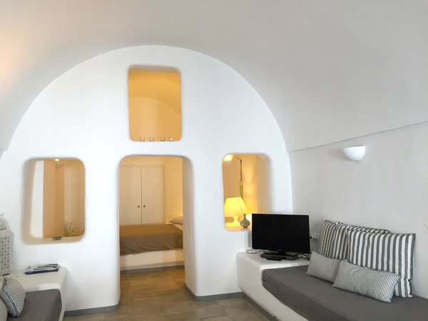 Located in the small village of Katerados, Il Melograno is a spacious two-bedroom yposkafo—a traditional Santorini-style cave house—with white-washed walls and a private sunlit courtyard.
