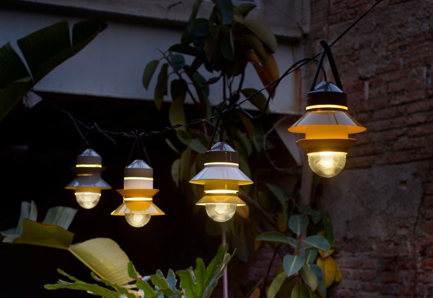 Marset's Santorini lights were designed by Sputnik Estudio in 2014. Available in white, gray, or mustard, the outdoor lamps are inspired by fishing boat lanterns and can be customized for your space—including how many shades to place on the diffuser, the order, position, and direction.  Photo 6 of 6 in Extend Your Time Outside With These 6 Innovative Lighting Designs For Your Outdoor Space