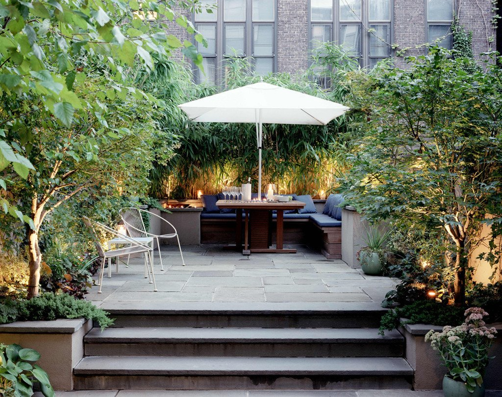 Elysian Landscapes modernized a classic brownstone by creating a private bi-level patio with clean, built-in seating for outdoor dining.  Photo 4 of 11 in 10 Modern Gardens That Freshen Up Traditional Homes