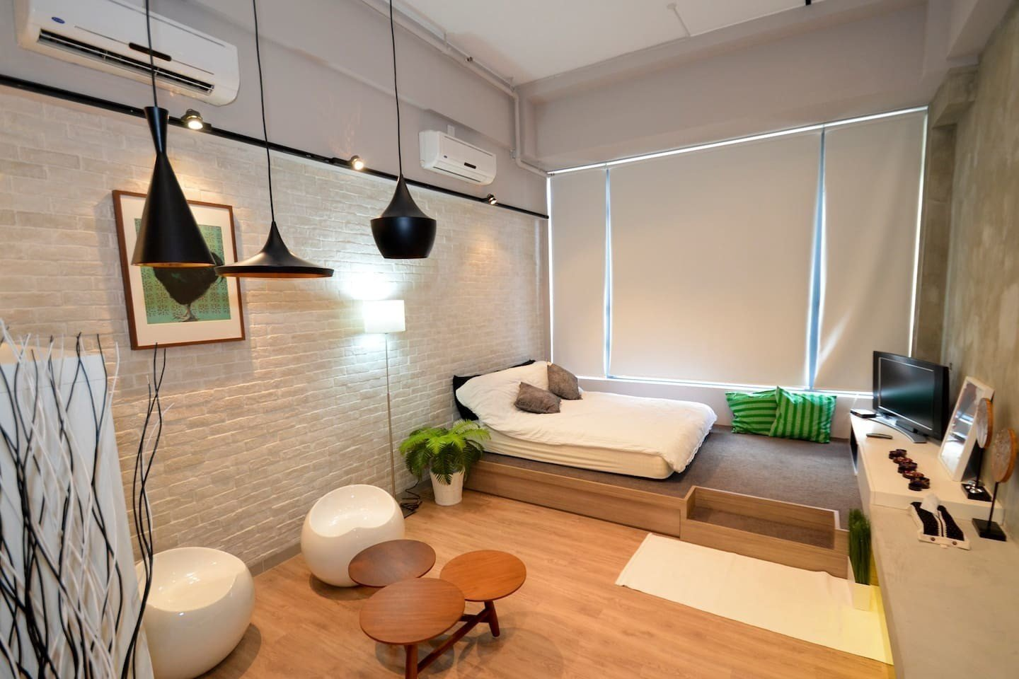With a double bed on a raised wooden platform, white washed brick walls and Tom Dixon pendant lights, this small 313 square foot studio apartment is perfect for single travellers or couples.  Photo 11 of 11 in 10 Modern and Stylish Places to Stay in Hong Kong