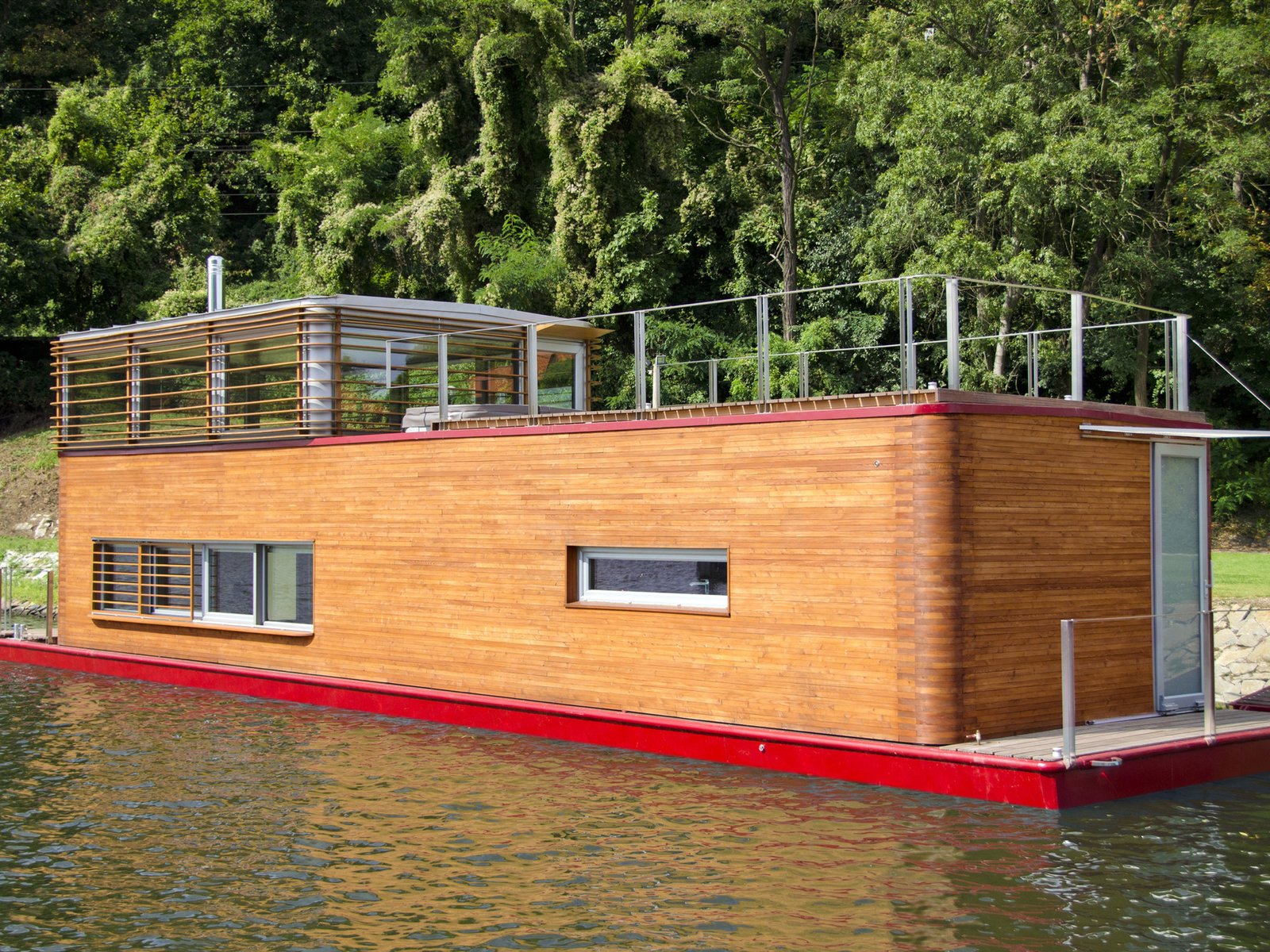 floating homes multilevel houseboat with wood siding and red trim
