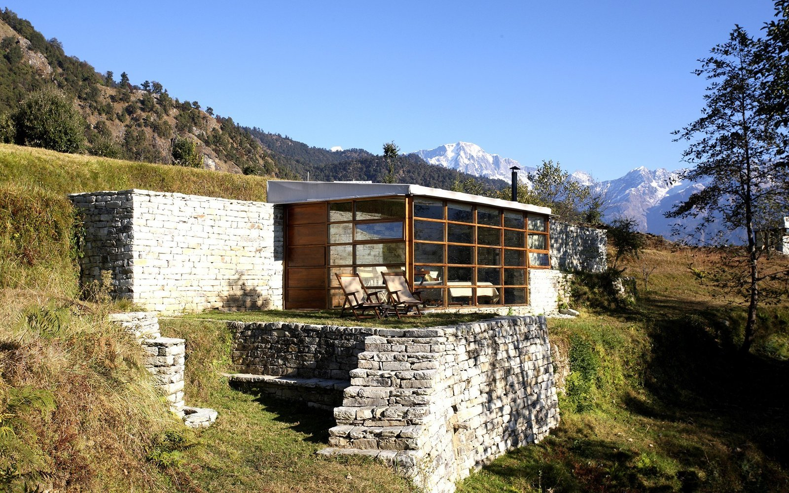 Outdoor, Trees, Slope, and Grass Enjoy fresh mountain air and get a bird's eye view of the Himalayas at Shakti 360º Leti – four private stone, glass and wood cabins high on the peaks of the India-Nepal border.  Photo 6 of 13 in Hide Out in One of These Asian Retreats That Are Immersed in Nature