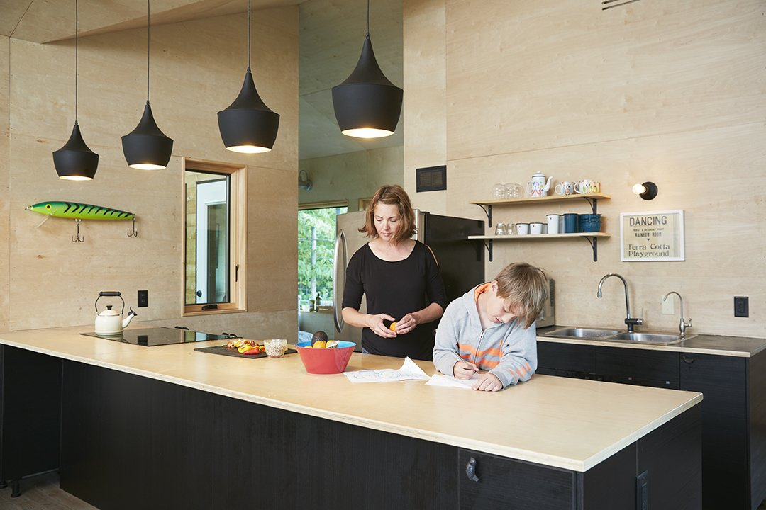 Kitchen, Wood, Drop In, Wood, Ceiling, Pendant, Wall, Refrigerator, and Range In the kitchen both the walls and the countertop are made of birch plywood. A quartet of black Tom Dixon Beat lights hangs overhead.  Best Kitchen Wood Refrigerator Wall Wood Photos from Hot to Trot