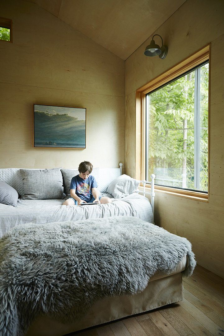 Bedroom, Bed, Bench, Wall Lighting, and Light Hardwood Floor Emerson, 8, reads in a sitting room where overnight guests stay.  The Land House from Hot to Trot