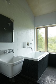 In the bathroom, the sink is by Kohler and the tub is by Maax.