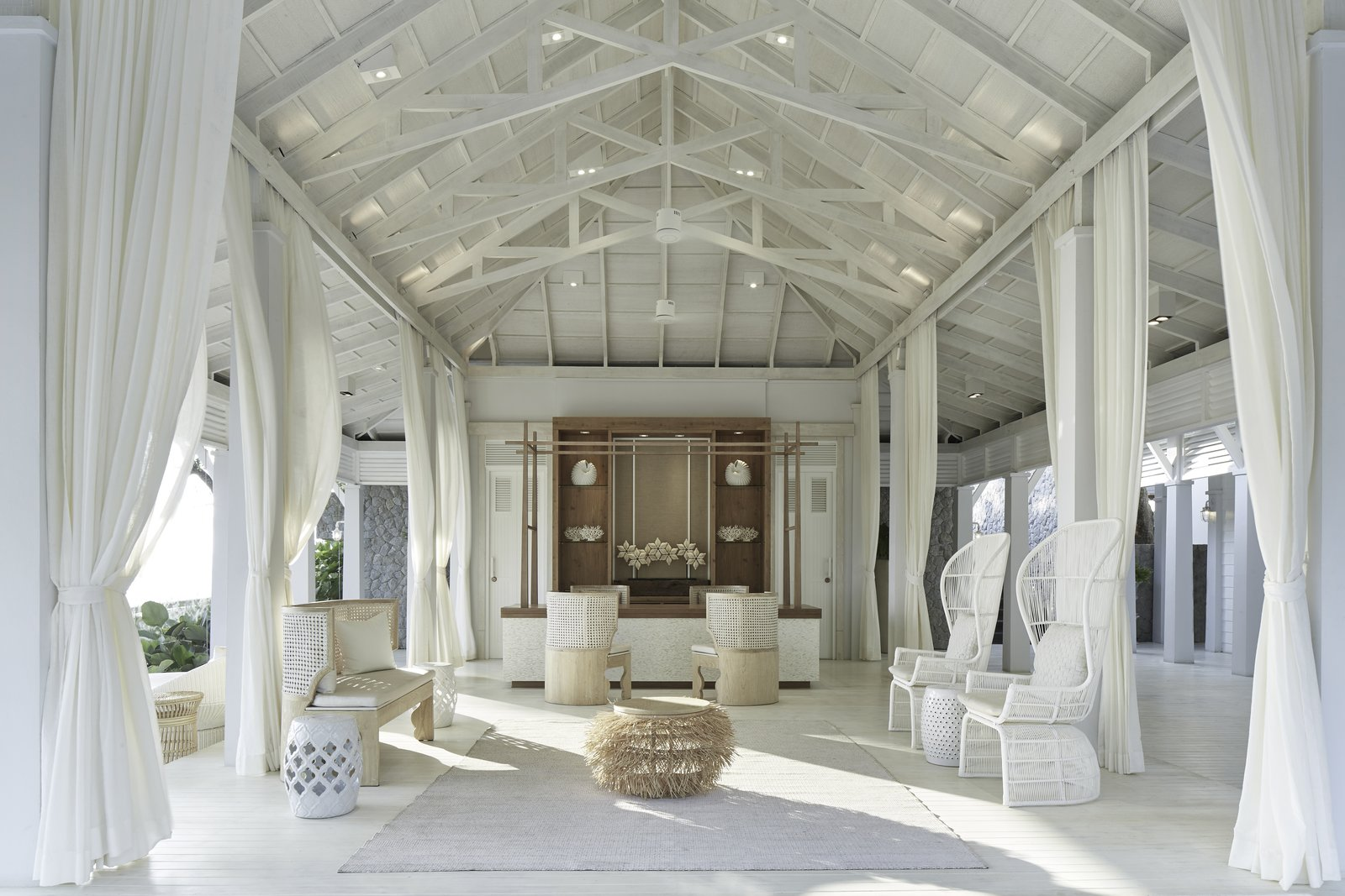 Living Room, Chair, Coffee Tables, Ottomans, Painted Wood Floor, and Ceiling Lighting A color palette of white, blue and grey along with white washed wood brings a breezy, tropical-nautical look to Cape Kudu Hotel on the peaceful island paradise of Koh Yao Noi in Thailand.  Photo 12 of 13 in Hide Out in One of These Asian Retreats That Are Immersed in Nature