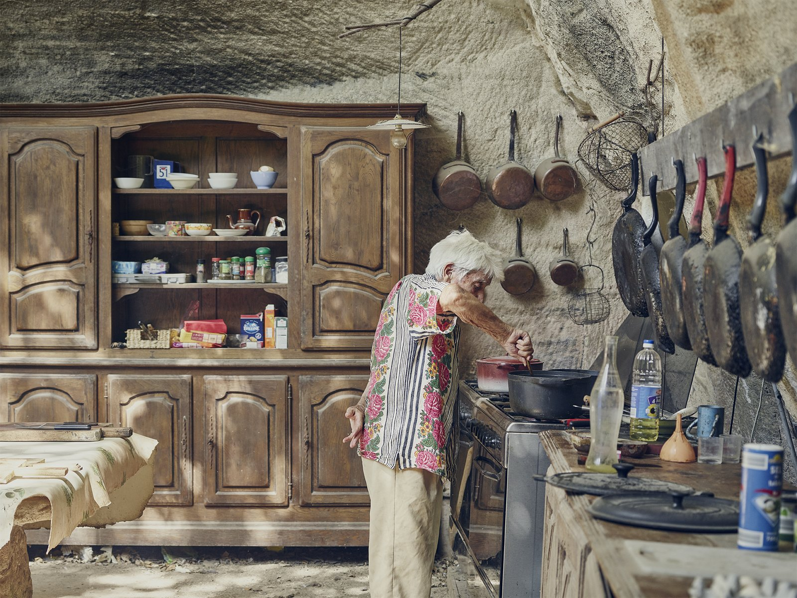 Kitchen, Wood Counter, Range, Pendant Lighting, and Wood Cabinet In the limestone kitchen embedded in the hillside, Lolo keeps only proven essentials—skillets that have been seasoned countless times and furniture that has been passed down for generations.  Photo 3 of 19 in Mine Dining