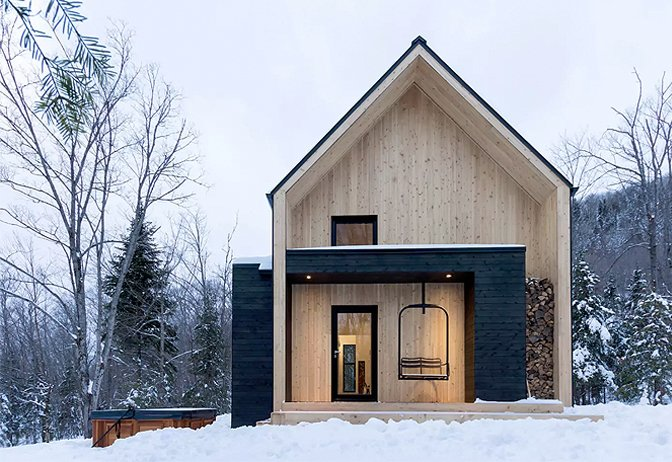 Exterior, Wood Siding Material, Gable RoofLine, and Cabin Building Type Just ten minutes away from Quebec's popular ski area – Le Massif de Charlevoix, this Scandi-inspired cabin is much larger than it looks, and can comfortable accommodate up to 14 guests.  Photo 3 of 10 in Get Back to Basics by Staying at One of These Modern Cabins
