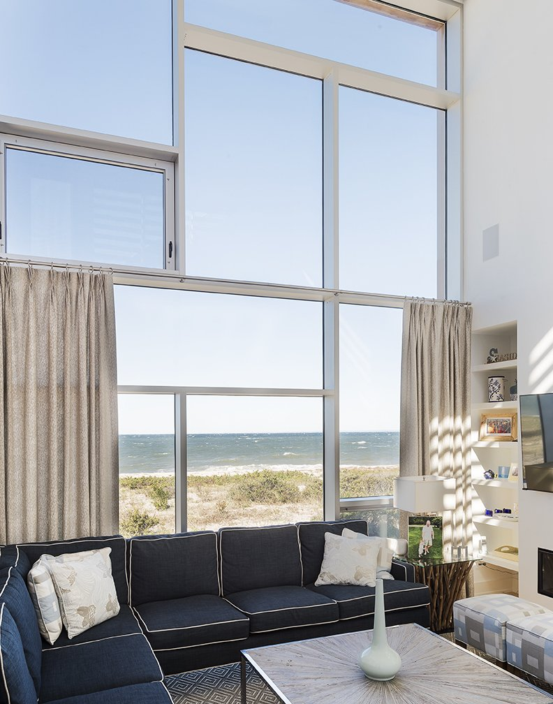 """""""We live in an old Tudor, so we've never had anything new. We said, 'Let's go for it—buy the land and make a house.' Little did we know what we were going to face."""" Bob Bombara, resident Tagged: Living Room, Sofa, Sectional, Coffee Tables, and Bookcase.  North Sea House from Shore Bet"""