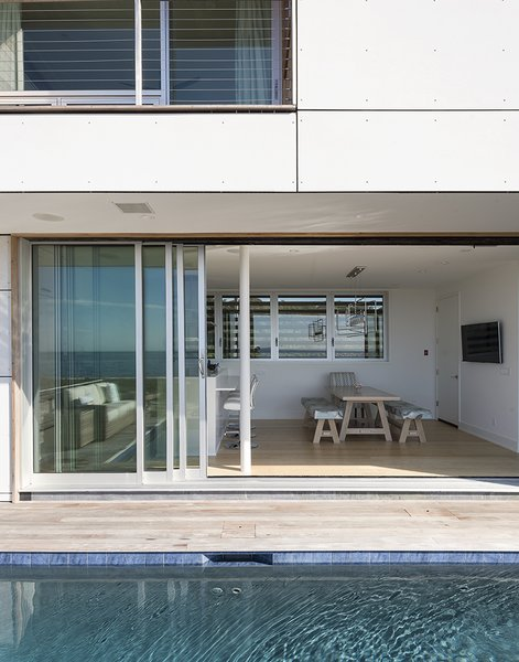 Outdoor, Front Yard, Back Yard, Side Yard, Swimming Pools, Tubs, Shower, and Decking Patio, Porch, Deck Having a strong outdoor element was also important.  A 32-foot-wide Solar Innovations sliding door connects the kitchen  to a deck and pool.  Best Photos from Shore Bet