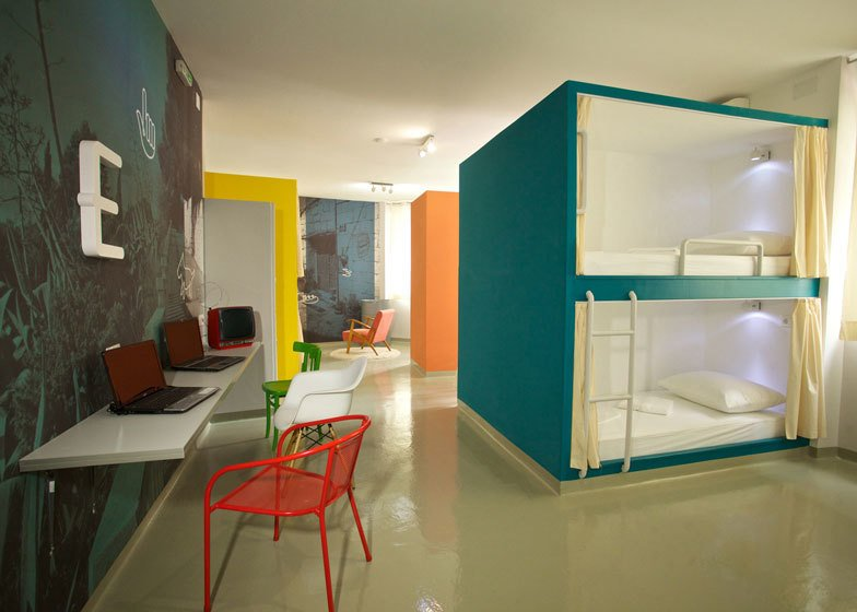 Two more units are located in a petite white room with an extra bed raised high above the flooring, resting atop stacked lockers. Tagged: Bedroom, Bunks, Ceiling Lighting, Chair, and Wall Lighting.  Photo 6 of 7 in 6 Well-Designed Hostels For the Minimalist Traveler