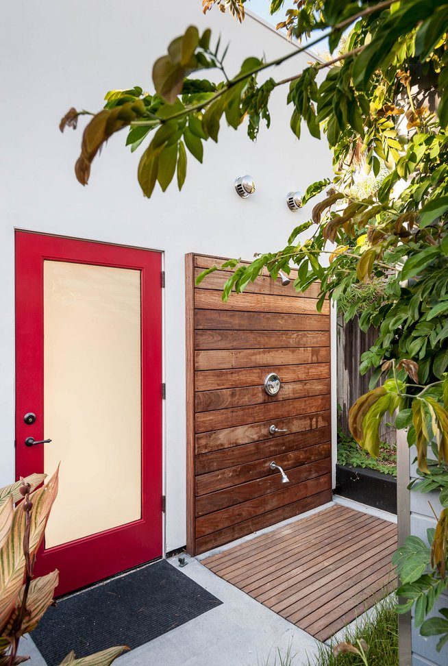 "Designed for easy beachside living, ""the cube"" in the backyard—essentially the renovated garage—sports a sleek outdoor shower complete with a teak deck and Moen fixtures.  Photo 6 of 14 in These 13 Outdoor Showers Will Make You Consider One For Your Own Yard"
