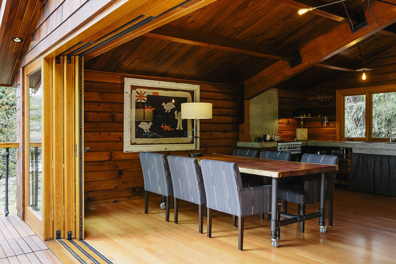 Dining, Chair, Table, Light Hardwood, Ceiling, Table, and Lamps On the main floor, custom sliders by Oakridge Windows & Doors open to a table and chairs designed by Paquette and built by Conrad Contracting. The wood paneling on the walls was salvaged from the original structure and resawn; each piece was scuffed with fine sandpaper and coated with Projectol.  Best Dining Light Hardwood Lamps Photos from An Eclectic Pacific Northwest Cottage