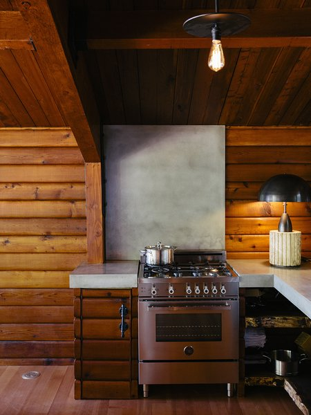 A Column lamp by Apparatus and concrete countertops join a Bertazzoni propane range. The brass pendant is by Workstead.
