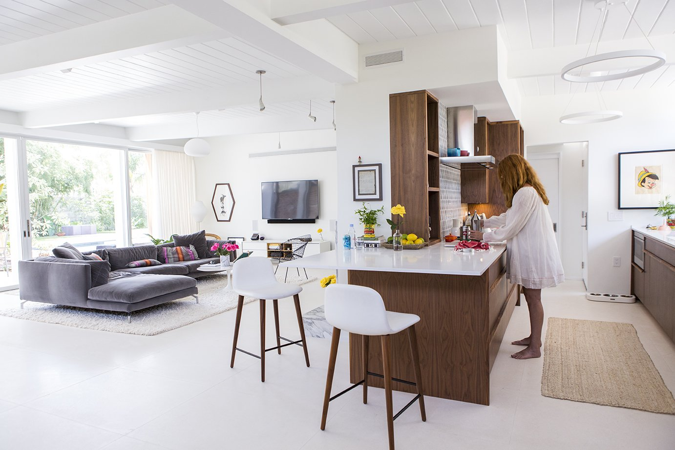 Kitchen, Engineered Quartz Counter, Wood Cabinet, Pendant Lighting, Ceiling Lighting, Accent Lighting, and Rug Floor A 1953 modern home by Curtis and Davis in New Orleans's Lakeshore neighborhood proved too tempting to pass up for veteran renovators Maury Strong, a film producer with an A-list client roster, and Ron Caron,  a public school teacher. But the couple soon discovered that the flood-damaged structure with multiple sloppy renovations was  a bigger challenge than they had imagined. With the help of a team led by Wayne Troyer and Natan Diacon-Furtado of studioWTA and the original architectural plans, they created a modern oasis to last a lifetime.  Photo 1 of 13 in Back to the Garden
