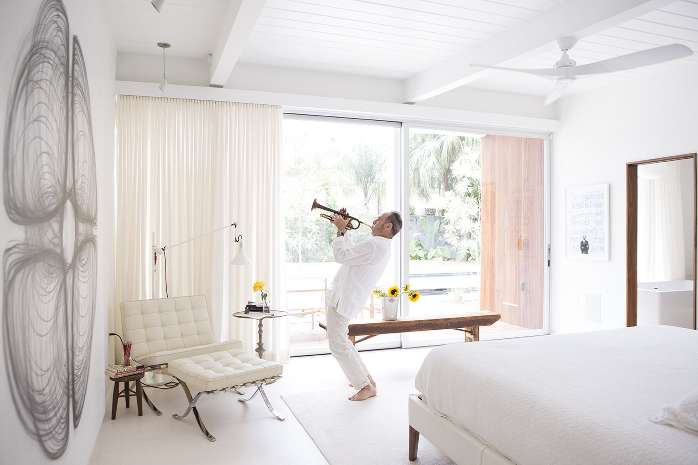 Bedroom Custom curtains by Katie Koch Home offer privacy in the master suite, where Ron plays the trumpet. The couple own a mix of new and vintage Mies van der Rohe Barcelona chairs.  Emerald Street Residence from Back to the Garden