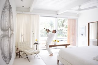 Custom curtains by Katie Koch Home offer privacy in the master suite, where Ron plays the trumpet. The couple own a mix of new and vintage Mies van der Rohe Barcelona chairs.