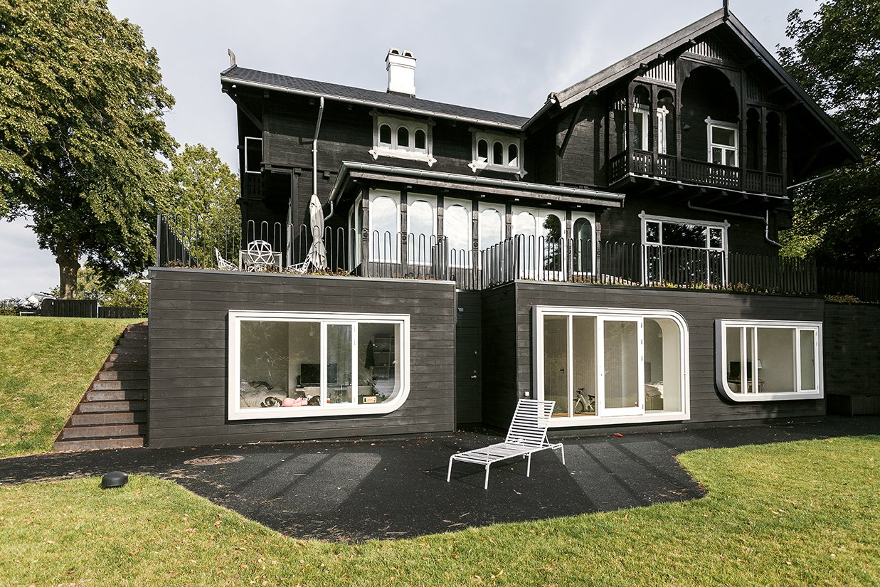 """The design team lowered the cellar floor by a foot and extended a rear-facade addition toward the lake. """"I am all for an architecture for its time—this house had a strong personality,"""" Jens says. """"The overscale windows create a tension, a dialogue...it's a new element, but one that celebrates the original idea.""""   Skibsted Residence"""