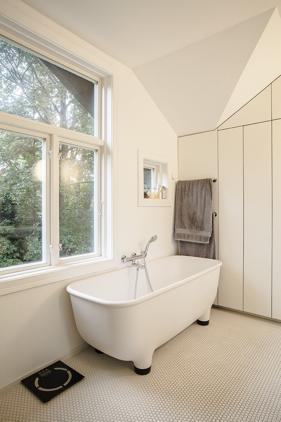 The footed bathtub in the completely renovated bathroom is by Marc Newson for Caroma.  Skibsted Residence