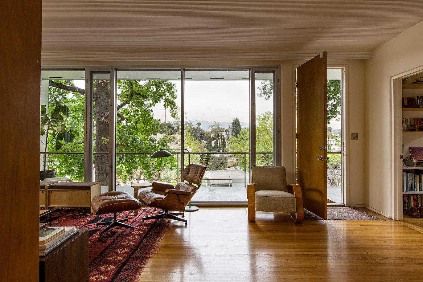 Living Room, Chair, Recliner, Rug Floor, Lamps, Floor Lighting, and Medium Hardwood Floor The front door is outfitted with a Saturn knob by Schlage; the same hardware was used as pulls at Lustig's June Wayne House.  Photo 7 of 14 in In Search of Alvin Lustig