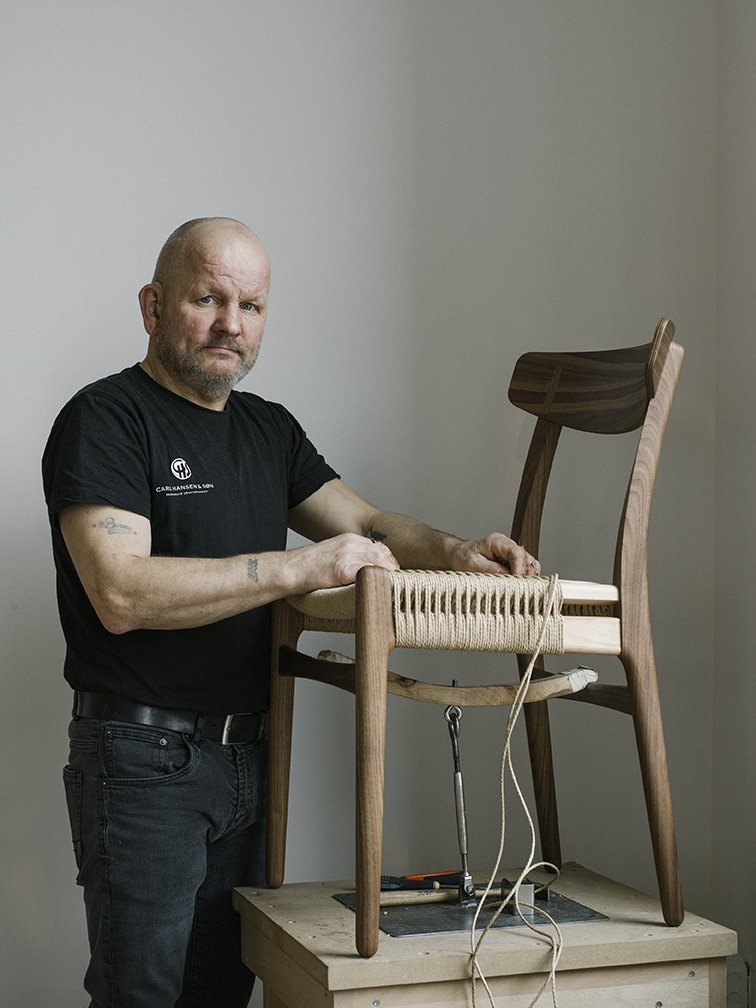 Master weaver Benny Hammer Larsen has  worked for Danish furniture company Carl Hansen  & Søn for more than two decades. He travels the globe, demonstrating the meticulous techniques used to realize each piece. He stands next to the  reintroduced CH23 dining chair, by Hans J. Wegner.  Photo 2 of 12 in Warp Speed