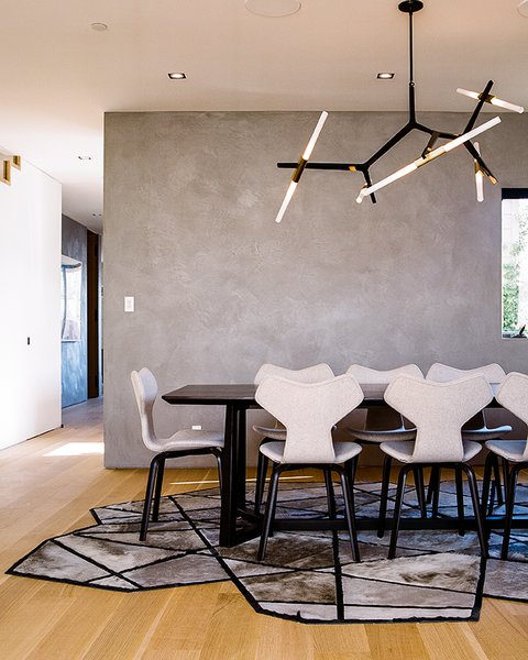 Fritz Hansen Grand Prix chairs, a Lindsey Adelman Agnes Chandelier, and a Kyle Bunting Runway rug furnish the dining room.