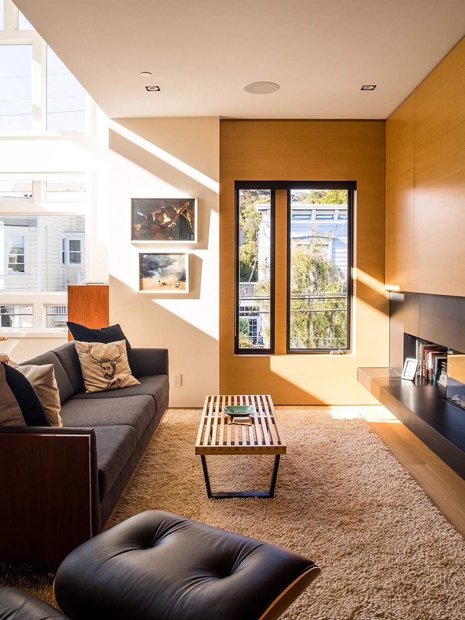 Living Room, Chair, Recessed Lighting, Bench, and Light Hardwood Floor In the living area, a restored Milo Baughman sofa and a Nelson Platform bench join an Ortal fireplace.  Photo 9 of 15 in Domino Effect: How a Bedroom Refresh Jump-Started a Whole-House Remodel For a Tech Exec