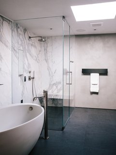 In the master bathroom, a freestanding Waterworks tub is paired with a Fantini fixture. Calacatta marble surrounds the shower; the flooring is Evolution ceramic tile from Apavisa.