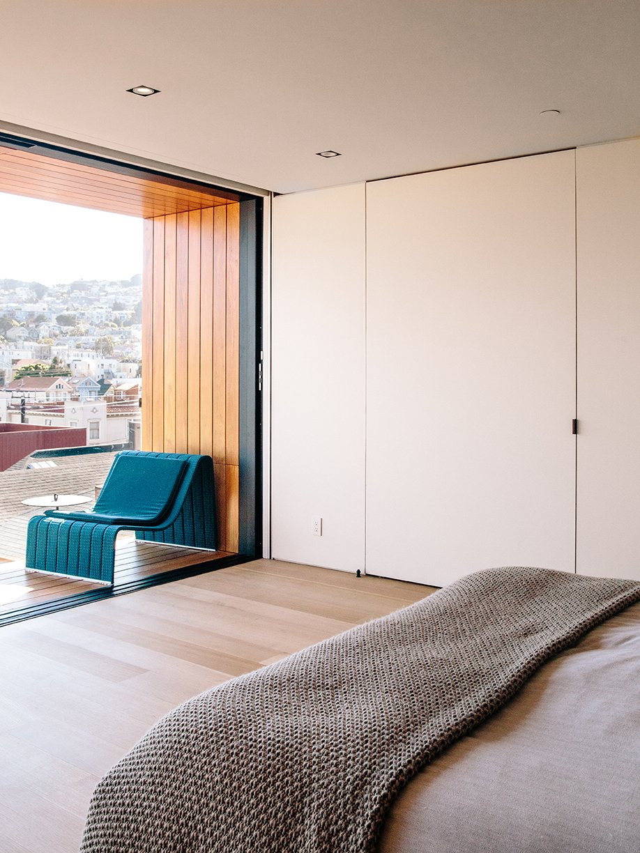 Bedroom, Bed, Storage, Chair, Light Hardwood Floor, and Recessed Lighting A special media door opens to reveal the bedroom's AV system.  Conrad Residence from Domino Effect: How a Bedroom Refresh Jump-Started a Whole-House Remodel For a Tech Exec