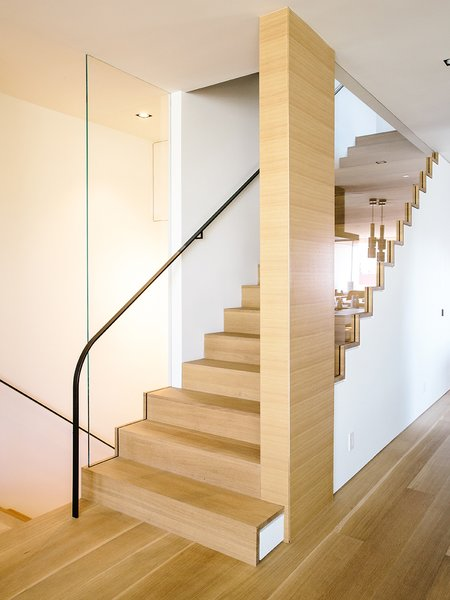 The staircase  follows the bedroom's new primary material, French white oak.