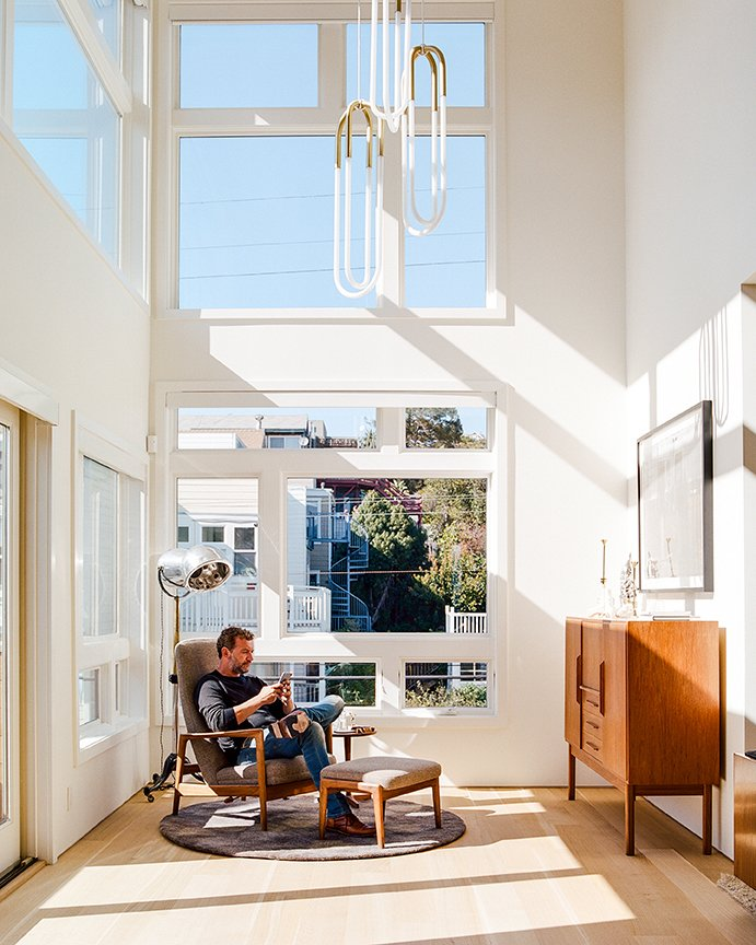 Living Room, Chair, Console Tables, Pendant Lighting, Light Hardwood Floor, and Rug Floor Tom and Kate own the top two  floors of the building. On the lower level, in the double-height foyer, Milo Baughman's Recliner 74 is positioned beneath Rudi Double Loop pendants by Lukas Peet for Roll & Hill. The floor lamp is a custom piece that De Angelis Designs adapted from a vintage salon hood dryer.  Entry from Domino Effect: How a Bedroom Refresh Jump-Started a Whole-House Remodel For a Tech Exec