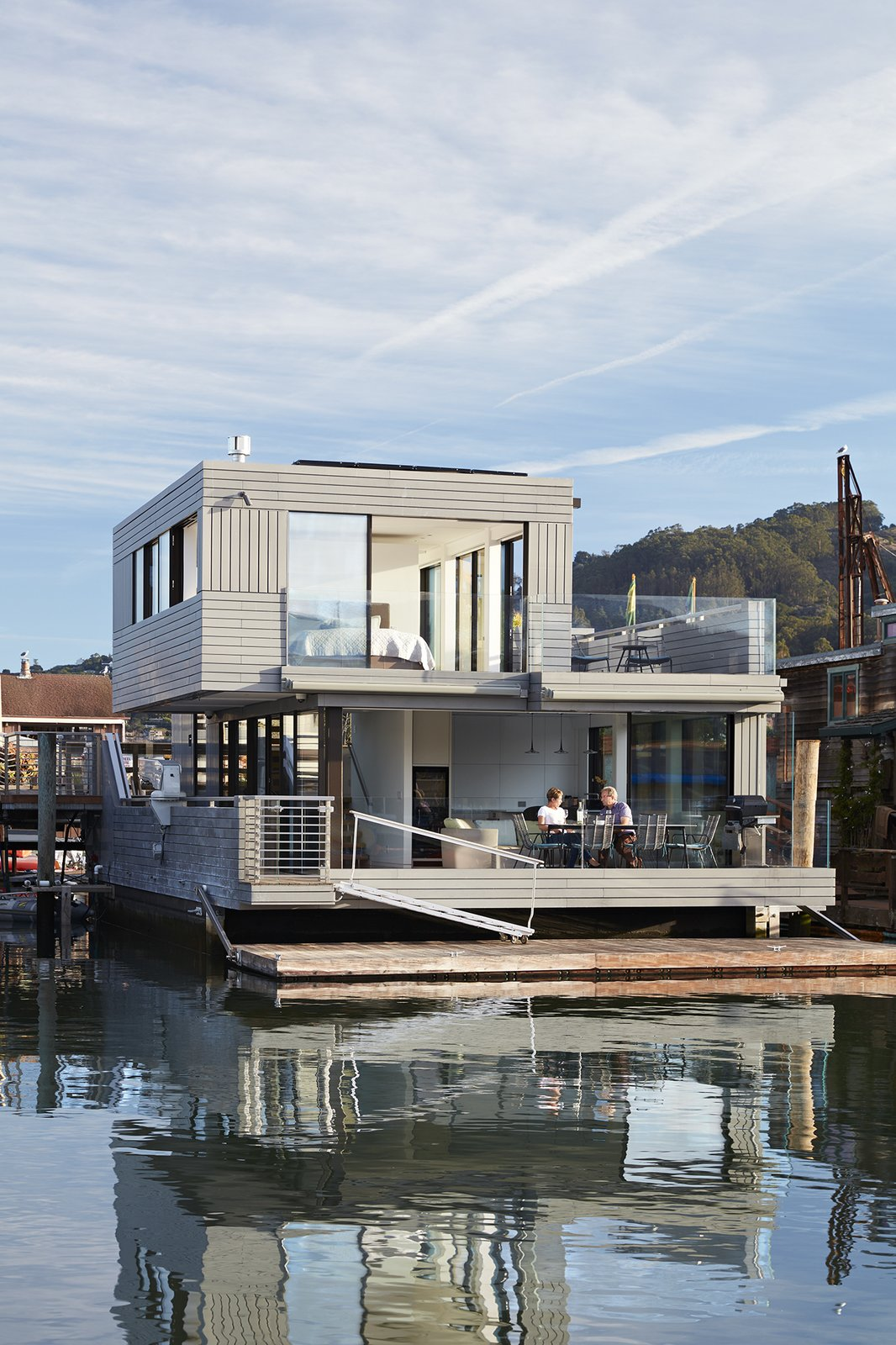 Large Patio, Porch, Deck, Hanging Lighting, and Outdoor Automatic retractable Sky-Frame windows open the living room  completely on two sides.  Floating Dreams Residence from Water Sports