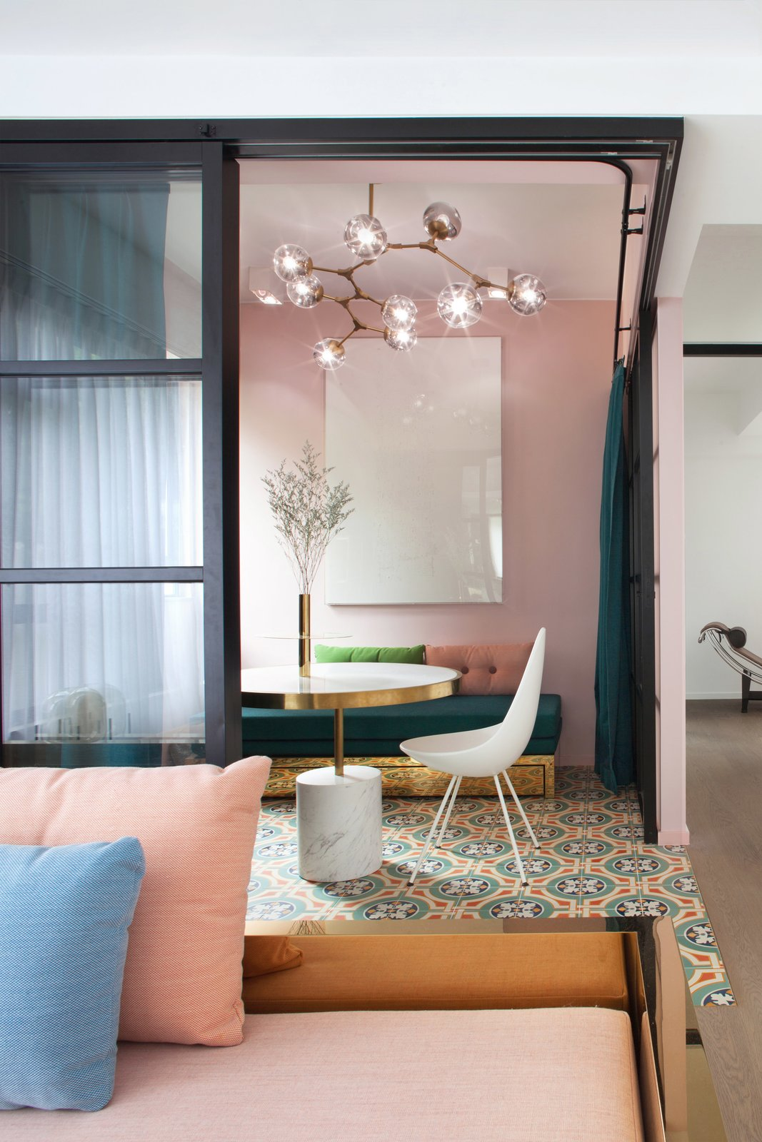 Living Room, Coffee Tables, Chair, Bench, Ceramic Tile Floor, Ceiling Lighting, and Medium Hardwood Floor Glass partitions framed in powder-coated metal slide back to make flexible use of the floor plan in a 1,206-square-foot apartment.  Photo 1 of 7 in See How This Colorful Hong Kong Apartment Was Made to Feel Bigger Than it Actually Is