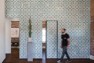 Off the living room, two small bedrooms and a bathroom can be reached through sliding doors that, when closed, continue the cheerful pattern of the Moroccan cement tiles covering the wall.