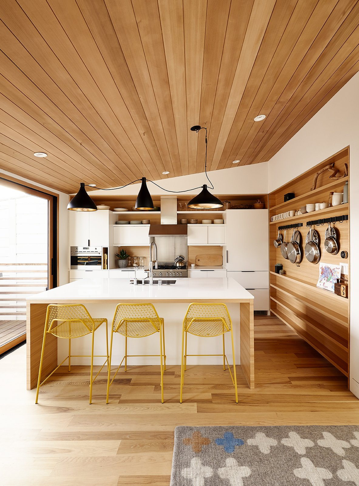 Light Hardwood Floor, Table, Chair, Wood Cabinet, and Kitchen Swell lights by Pablo hang above Hot Mesh stools from Blu Dot. The millwork is by J. Spix Fine Cabinets.  Best Photos from A Renovated Tiny Victorian with 21st-Century Interiors